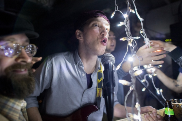 Robb Carr (center), guitarist of Rochester, N.Y. band Buckets, sings before the start of a basement show in downtown Rochester on November 11, 2012.