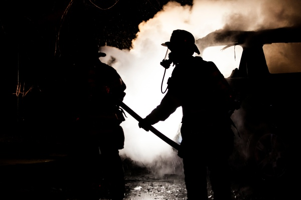 Rey Palacios feeds hose to Antoine Brady at a suspected arson in the parking lot of the UAW off Dewey Avenue just after midnight on the morning of January 24th 2013 in Rochester NY.