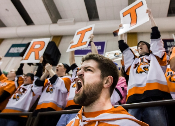 Rochester Institute of Technology Student Ryan Kinney (center) of Boston, Massachusetts cheers on the Men's Ice Hockey team in the final minutes of a game versus Bentley University.  The Tigers shutout Bentley 4-0.