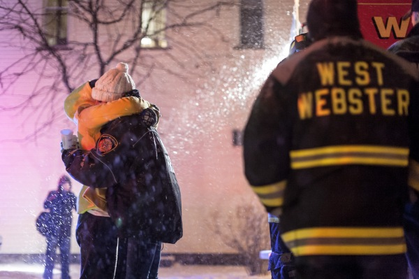 [POTW Weeks 4-5, First place] In Webster, NY, a West Webster firefighter receives an embrace upon arriving at a vigil held for two West Webster volunteer firefighters, Tomasz Kaczowka, a 911 dispatcher in his early 20s, and Michael Chiapperini, a 43-year-old lieutenant with the Webster Police Department, December 26, 2012. After arriving at a car fire which set ablaze seven homes on Lake Rd, both men were killed after being shot at on the morning of Christmas Eve by 62 year old William Spengler. The vigil was organized by the owners of Barry's Old School Irish restaurant on Main Street in Webster