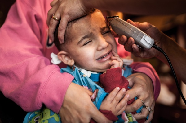 2 year old David Quick is held down by his mother Vanessa Quick as Junior, a barber at Top Notch Barbering salon in Rochester's Swillburg neighborhood gives him his first haircut, Friday, January 25, 2013.