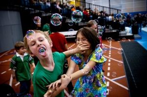 Tagan Merkley, 11, pushes Alyssa Troidl, 9, out of the way to eat bubbles during intermission at the Roc City Roller Derby event in Gordon Field House, Rochester, NY on March 24, 2012.