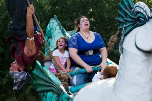 "Alissa Wilson, 20, of Appleton, Mich., screams as Gabriel Nottage, 27, of Fort Lauderdale, Fla., operator of The Seahorse, flips upside down on the ropes of the moving ride at the Michigan Renaissance Festival in Holly, Mich. on Aug. 26, 2012. ""I just wanted to go on to make sure she was okay,"" said Wilson, who accompanied her 5-year-old sister on the swing, after her fear of heights ended up getting the better of her."