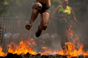 A woman leaps over flames to complete one of the last obstacles during the Warrior Dash 5K run in Genesee, Mich. on Saturday, July 28, 2012. Over 25,000 runners competed during the two-day event.