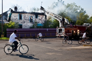 Spectators ride their bicycles in circles around a parking lot adjacent to a vacant home that caught fire in Flint, Mich. on Aug. 23, 2012. Flint has a population of about 100,000, down nearly 20 percent since 2000. Foreclosures are high and more than a quarter of the 14,000 residential properties in the city have been abandoned. That has led to another grim statistic: The city has the highest per capita arson rate in the United States.