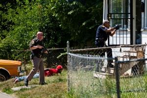Police enter a home after receiving reports of gunfire on the street in Flint, Mich. on June 26, 2012