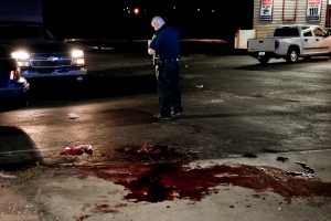 A Flint Police Officer stands in the parking lot of the Quick Pick Party Store where a man was fatally shot in Flint, Mich. on July 16, 2012. Neighbors who saw the aftermath of the shooting said the man repeatedly tried to stand up, struggling with paramedics as they attempted to treat him.