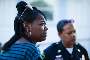"Gun Violence in Flint - Visiting family in Flint, Mich. after moving from the city 25 years ago, Mary Evans, of Pine Bluff, Ark., stands at the edge of the crime scene where a drive-by double shooting left her cousin and another woman in critical condition on July 11, 2012. ""I came to visit and now I have to go through this,"" said Evans, ""I'm back three days and this is what happens... She didn't deserve this."""