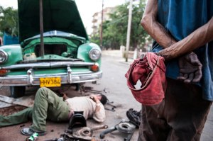 On Saturday, February 23rd, 2013, two men work on fixing one of their old cars, in Havana, Cuba.