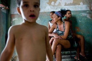 On February 27th, 2013, Lairo Alejandro-Movil, Natacha, Nairi and Yohara sit in the front entrance of their home in Old Havana, Cuba.