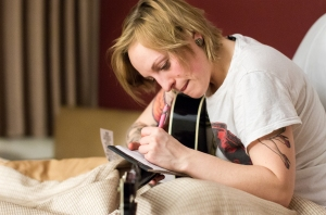 "Becca writes down lyrics to an untitled song while staying at a local motel. Becca lives with her sister Rachel and her husband, Alan Hammond in a two-bedroom apartment in Rochester, NY. ""Sometimes I just need to leave and get some space."""