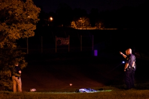 Gun Violence In Flint - Police officers investigate the scene of a fatal shooting that took the life of 51-year-old Willie D. Kidd Jr. on North Saginaw Street next to the Berston Field House community center in Flint, Mich. on Sept. 17, 2012.