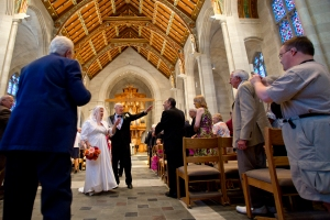 Joyce and Frank wave to family and friends as they walk down the aisle as Mr. and Mrs. Maslyn at Sacred Heart Cathedral in Rochester, NY. (Photo by Autumn Parry)