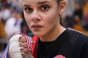 Celina Carissimi of Geneva Boxing Team just after winning her 3rd title fight at the 30th annual New York State Silver Gloves boxing tournament in Rochester December 1, 2012. Celina Carissimi is a 3 time New York State Boxing Champion. She is also fifteen. Still learning who she is Celina is many conflicting things at the same time: she is tender and tough, cocky and demure, brazen and reserved. Without giving away too much she has expressed that her home life leaves much to be desired and through the Geneva Boxing Team she has found a second family; one that is reliable and maybe more understanding. At the gym she is the only female boxer, which allows her to be special. The Geneva neighborhood Celina is from is not one that rewards excellence or even being different so she is constantly walking a thin line of celebrating her accomplishments and staying true to her roots. As she grows and moves forward her challenge is navigating these nuanced situations.  She is a person in flux; she's fifteen.