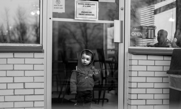 A child presses up against the door of Peppy's Too, a hamburger and ice cream stand just outside of Waterloo, NY, after finishing his ice cream.