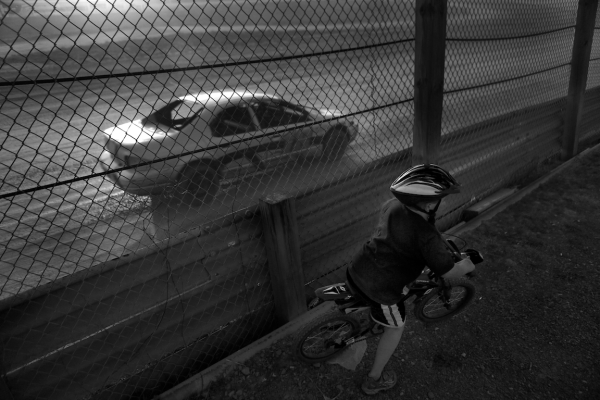 A child pretends to race along side a modified car racing at Paradise Speedways in Geneva, NY.