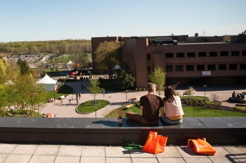 Seth Bauer, 19 1st year Photojournalism major, and Catalina McKay 3rd year Medical Illustration major, sit on the roof and watch as the last attendees leave Imagine RIT on the Rochester Institute of Technology campus in Henrietta, NY, on Saturday, May 4, 2013. (Photograph by Kate Lovering).
