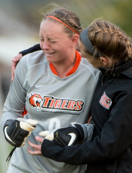 Rochester Institute of Technology goalkeeper Amanda Murray, left, is comforted by goalkeeper coach Katie Dry, right, after a 2-1 loss to Skidmore on Friday, Oct. 18, 2013 at Tiger Stadium  in Henrietta, N.Y. Skidmore scored in the last minute of regulation to win a key conference game. Photo by Josh Barber