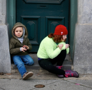Two children playing with cigarettes at the annually Mummer's Day Parade in Philadelphia Pennsylvania. The Mummer's Parade is the oldest folk festival in North America. Photo by Joe Phillipson