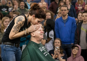 Jenna Buckton Hollenbeck kisses Roc City Roller derby volunteer Steve Strassner on his head after he has his hair shaved off to raise money for cancer awareness during halftime at a bout in the Gordon Field House in Henrietta, New York on March 23, 2013. Photo by Tom Brenner