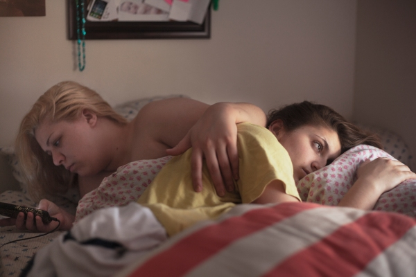 Hannah Kanik, 20, checks her phone while her girlfriend, Courtney DiStasio, 20, looks out the window when they wake up in the morning. Courtney and Hannah's relationship have been both affirming to one another, but Hannah's turbulent lifestyle leaves Courtney drained sometimes. Photo by Evan Ortiz