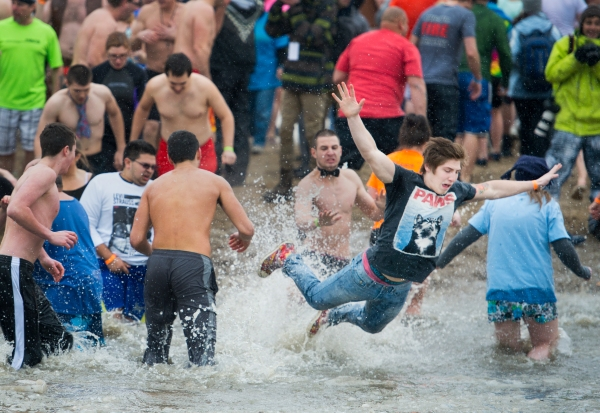A young plunger belly flops into icy water during the Rochester Polar Bear Plunge at Charlotte Beach in Rochester, New York on February 9, 2014. Photo by Tom Brenner