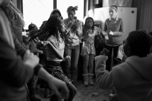 "Nadine Scholastique, 12, a Congolese refugee born in Zambia, dances in the kitchen during lunch as a volunteer plays music. ""I used to love going to church in Africa. We would sing and dance for hours until we were so tired we just fell asleep right there,"" recalled Nadine."