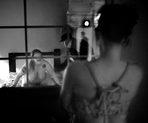 """Gawkers gaze as River (27) is caned by Geist-Der-Ruhe, (22). This private room at the dungeon is observed on closed circuit television by the dungeon monitors. (Geis-Der-Ruhe translates from German to """"spirit of calm"""")"""