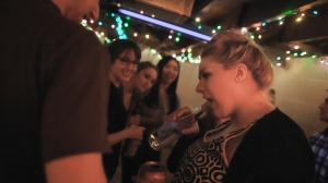 Hannah tries to open a bottle of alcohol for friends at party. People sometimes associated Hannah with drinking, a reputation developed from her partying.