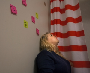 Hannah sits in her bathroom floor feeling overwhelmed before class. Sometimes she puts sickies on her wall to remind herself of what she needs to do. For Hannah, many of normal daily tasks are extraneous.
