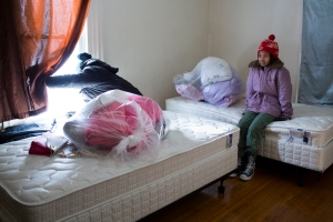 Aline Kamali, 10, right, sits in her new bed room as her mother looks out at the snow-covered neighborhood. The family was surprised that they would each have their own bed, as they used to sleep with 2 or more people per bed when they lived as refugees in Ethiopia.