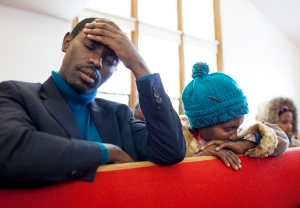 "Muhire and his sister Nyirazana Munyarugero pray during a service at the Genesee Park Seventh-Day Adventist Church in Rochester, NY. ""It will all be okay in this country once we find a church,"" Muhire said before finally finding a Seventh-Day Adventist Church, the denomination they attended when living in Ethiopia."