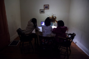 Dyna, Aline and Nyota watch Disney channel on a small television in the dining room. For one month, the children stayed in the apartment everyday before beginning school.