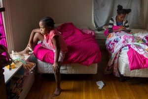 Nyota, left, looks out the window as Aline does her homework with a calculator in their bedroom.