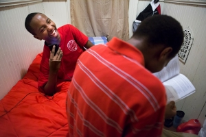 Sako, 14, laughs as he talks on the phone with a friend from Africa that has now resettled in Michigan as Serge studies a driver's manual in hopes of getting his learner's permit.