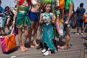 A young girl waits to continue walking with a group of attendees of Coney Island's annual Mermaid parade hosted on June 22, 2013, Brooklyn, NY.