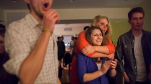 Hannah holds on to Courtney as they watch friends sing at a birthday party. With Courtney around, Hannah feels she is able to be more social in a healthy way and feel more reason to leave the house.