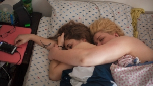 Hannah and Courtney embrace each in bed. Their relationship provides stability in each other, and although Hannah has a long way to go in her search for acceptance in herself, Hannah sees people are worth staying alive for.