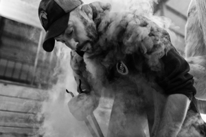 """Smoke engulfs Paul Batz while he """"hot fits"""" a horseshoe at Shooting Star Farm in Livonia, NY, on October 20, 2013. The hot steel does not hurt the horse during the process, in fact, when done properly, the horse cannot even feel it."""