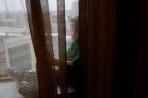 Following a 13-hour day of competitive cheerleading, Adwen Lorkovich (CQ,) five, sits in the windowsill of her family's hotel room in Buffalo, NY. Adwen and two of her older siblings have been cheerleading for one year.