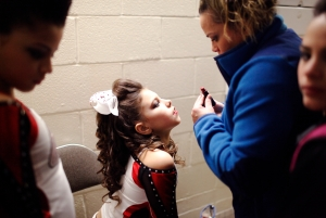 "Alita Vargas (CQ,) 10, of Rochester, NY, sits in the bathroom prior to competing in American Majestic, a National qualifying competition for varsity cheerleaders. ""I love everything to do with [cheering,]"" she says. Alita has been competing for two years."