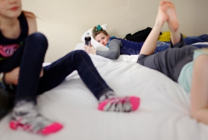 "Jennifer Holfeltz, 40, rests following a 13-hour day of varsity cheerleading in Buffalo, NY, on March 1, 2014. Three of her daughters cheer competitively. ""They eat, breathe, and sleep this,"" she commented."