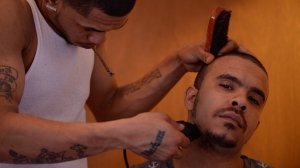 """Marcus Montreal (27), of Rochester, NY, shaves his band member Ricardo Murray (27), of Rochester, NY, in his home the day before they perform their second live show, on April 27, 2014.  Ricardo and Marcus are members of New Tren Gang, an aspiring hip-hop group founded in Rochester, NY.  According to Ricardo, """"This show is gonna be the start of something for us"""". Photo by David Falconieri"""