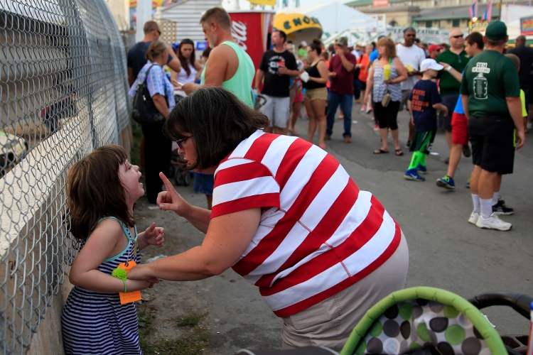Kelly Melzer, left, is yelled at by her mother, Katy, right, after Kelly had a screaming tantrum on the fairgrounds, on Saturday, August 30, 2014 at The Great New York State Fair in Solvay, N.Y.
