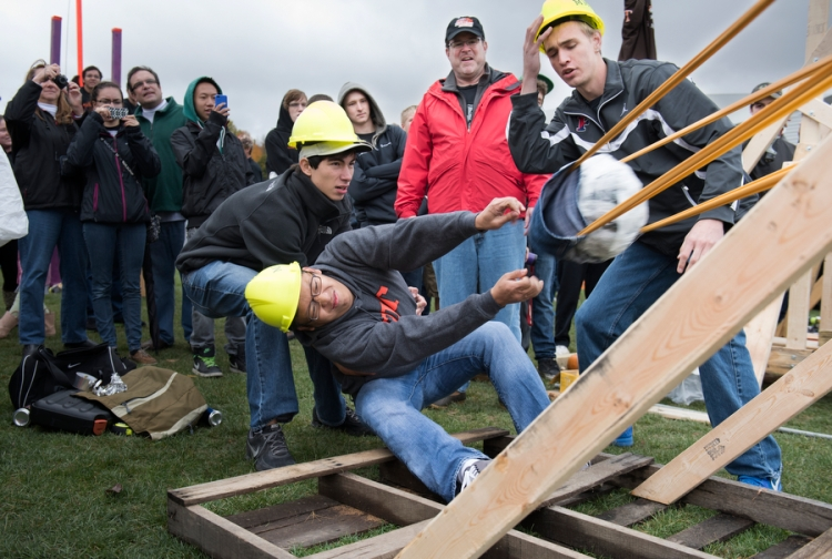 1st: Matthew Pronko assists Daniel Lim in firing off their slingshot during the Pumpkin Chunkin' with their teammate Adam Pries on October 18, 2014. Students, family, and friends attend Pumpkin Chunkin', an event where Mechanical Engineers create slingshots to launch pumpkins. The event took place at Rochester Institute of Technology during RIT's Brick City Weekend on October 18, 2014.