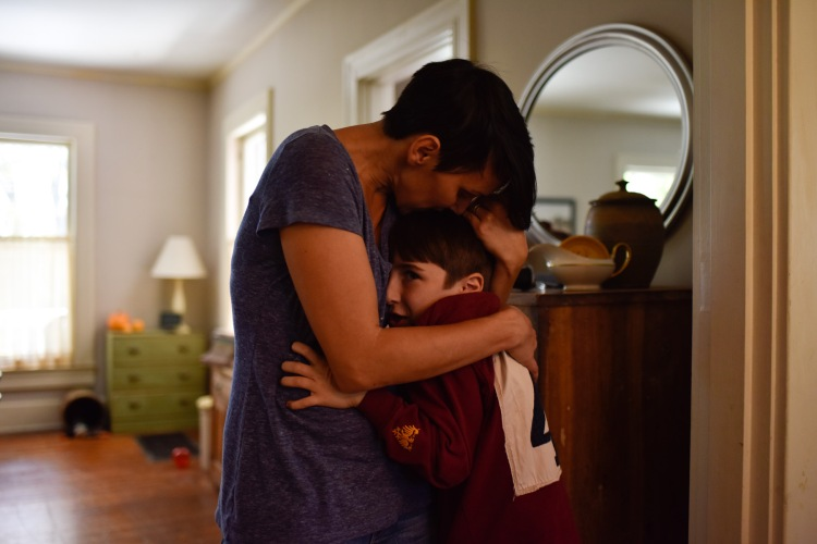 Laura Poulette embraces her son, Isaac Deaver, before leaving him at his grandmother's home for formal home-schooling.