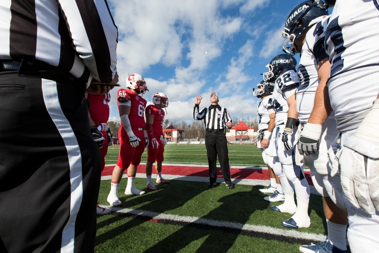 Captains of Ithaca and Cortland football teams  watch the coin toss before the football game on November 15, 2014.