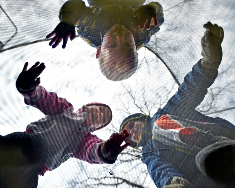 Kolton Montague, right, 5, jumps on a trampoline in the backyard of his home in Avon, N.Y., with his  siblings Kellan, top, and Kaelyn, left, both 2, on Nov. 16, 2014.