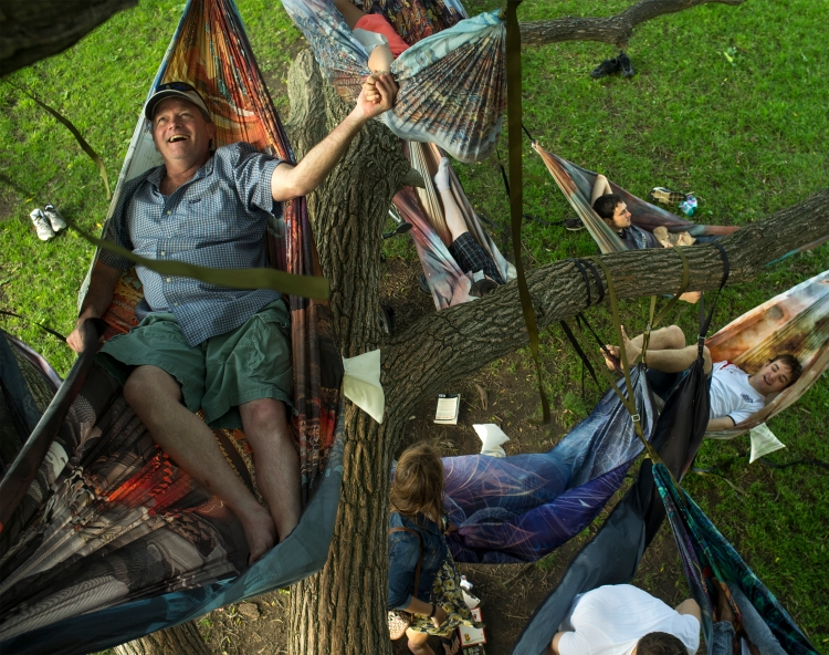 "Robert Langley, of Andover, Mass., holds the hand of his daughter Sarah, 9, as they hang in a web of  hammocks, being sold by a vender, that they came across while walking down the the Charles River Esplanade in Boston, Mass. on June 14, 2014. ""We're not telling your mother about this"", Robert said to Sarah."