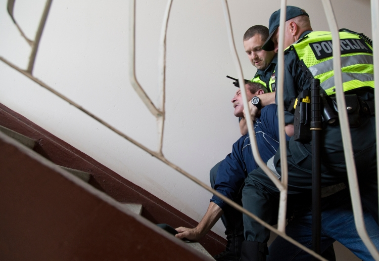 "Vilnius police officers Zilvinas Adomaitis and Andrey Gubanov react to a man resisting arrest in an apartment stairwell. The drunk man's wife, who claimed her husband threatened to kill her, made the call for police; however, she did not want to press charges. This was one of two calls that day involving a drunk man threatening his wife. He was legally drunk based on the breathalyzer test. Based on figures from the World Health Organization's recent ""Global Report on Alcohol and Health 2014,"" Lithuania is listed as the third heaviest drinking country in the world. Among other things, alcoholism is seen as a contributing factor to Lithuania's suicide rate."